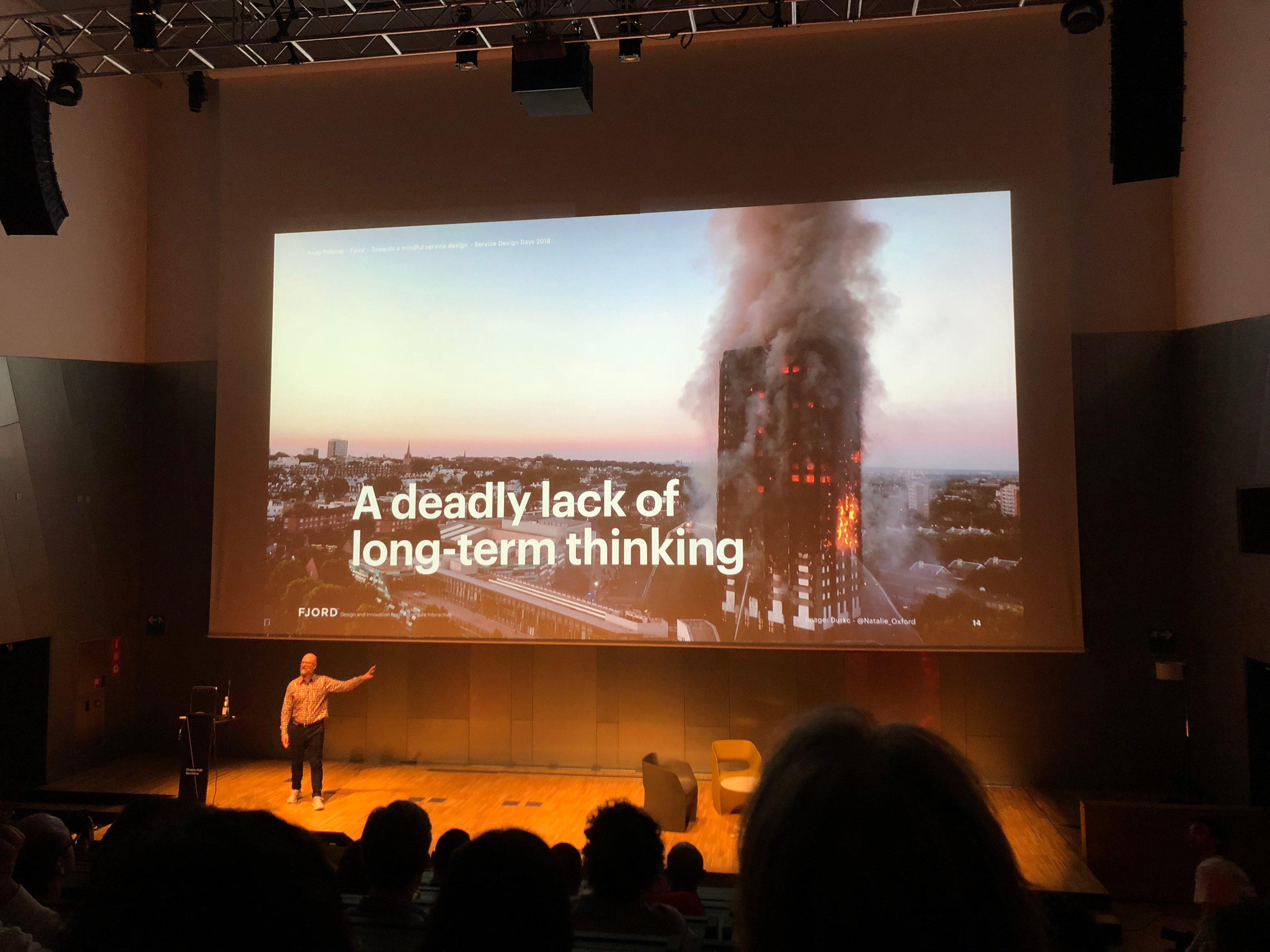 """Andy Polaine viser bilde av en blokk som brenner. På bildet står det """"A deadly lack of long-term thinking""""."""