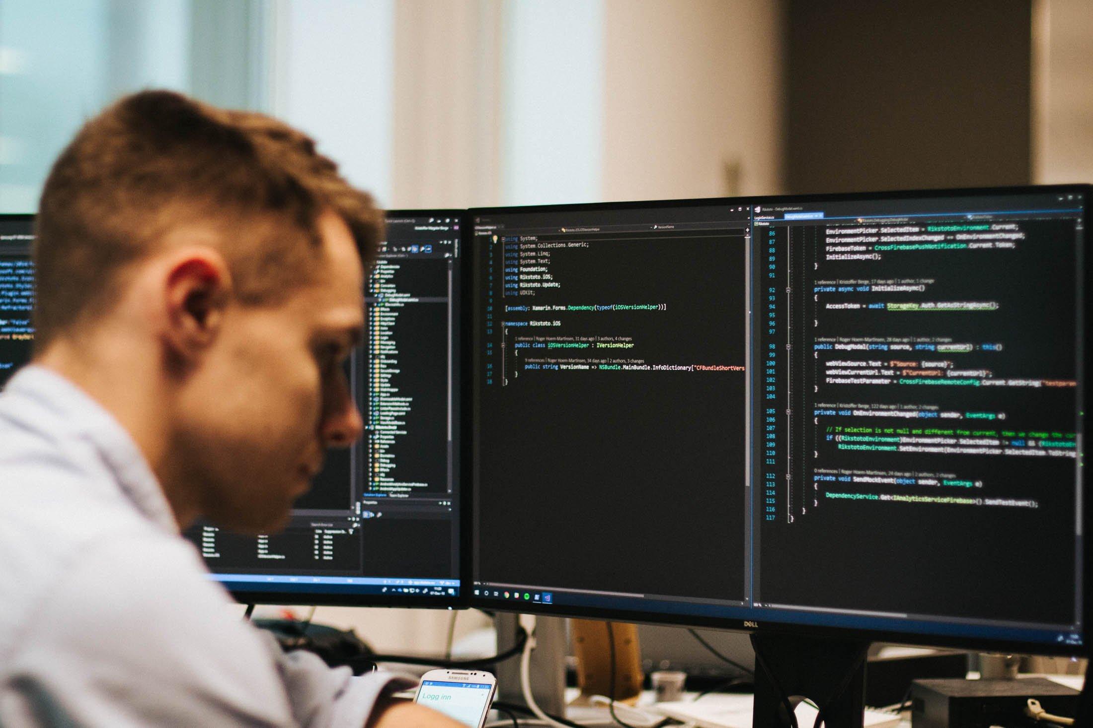 Kristoffer koder på to desktoper