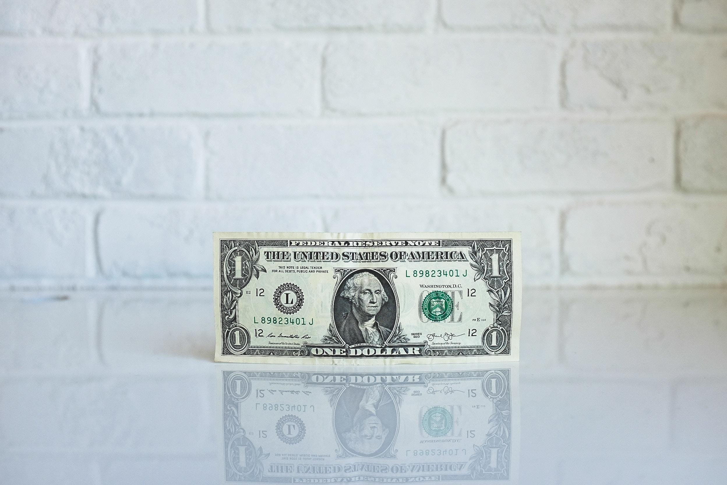 Bilde av en dollarseddel inntil en vegg. Bilde er tatt av NeONBRAND og ligger på nettsiden Unsplash.