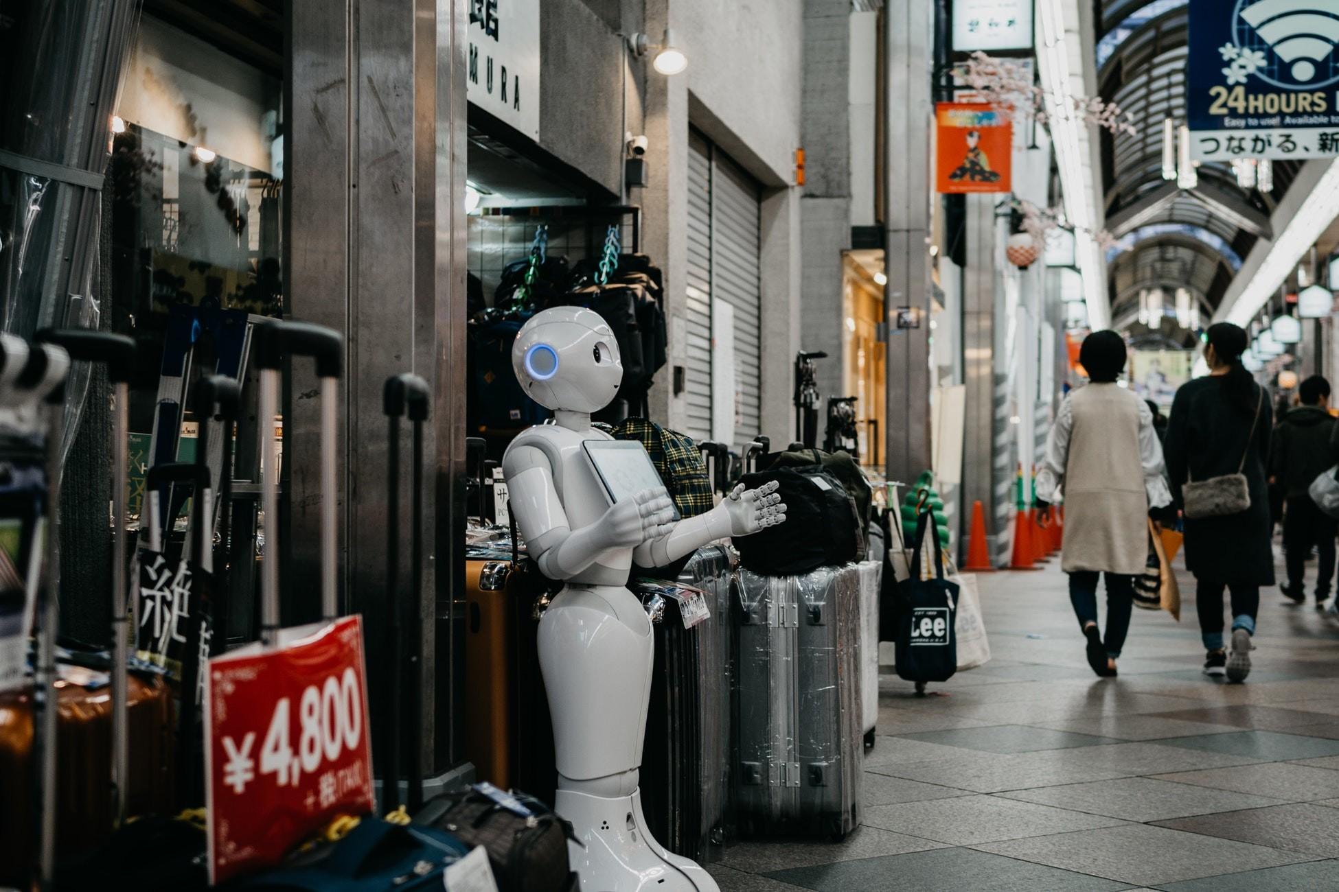 Robot som står utenfor en butikk og tilsynelatende ønsker velkommen