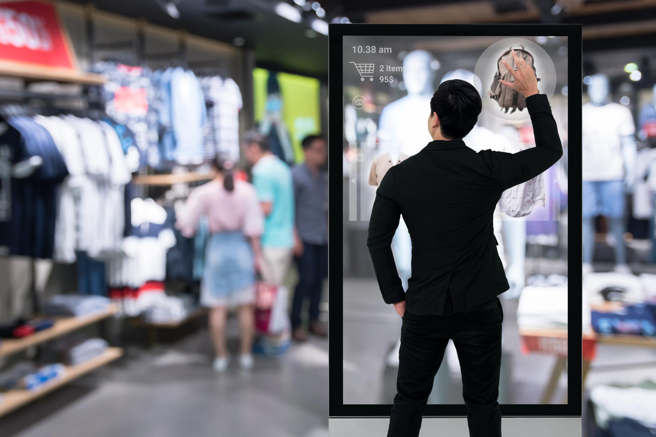 En mann kommuniserer med en stor skjerm inne i en fysisk butikk